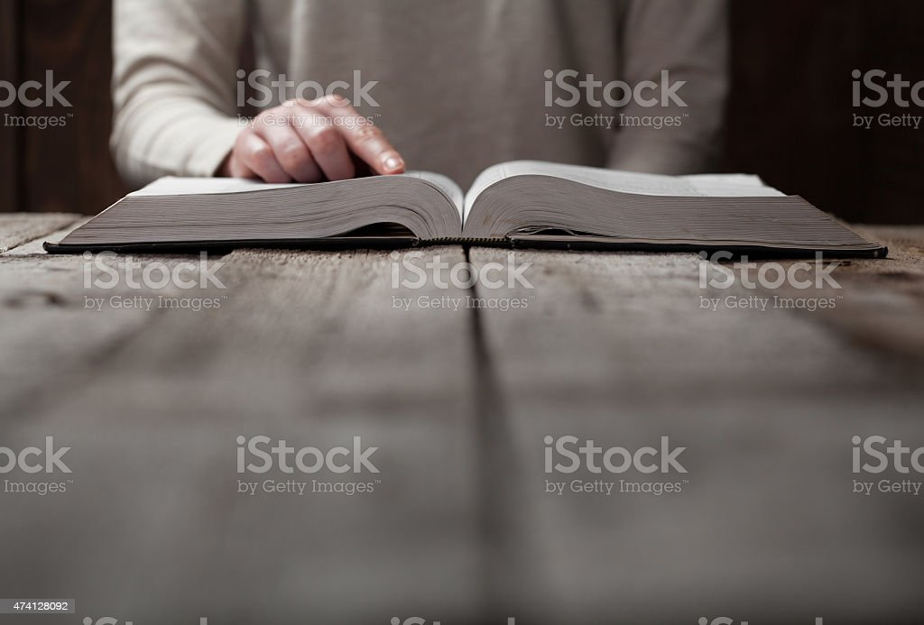 Woman reading a Bible and following with her finger stock photo
