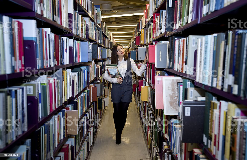 Woman reading a book at the library stock photo