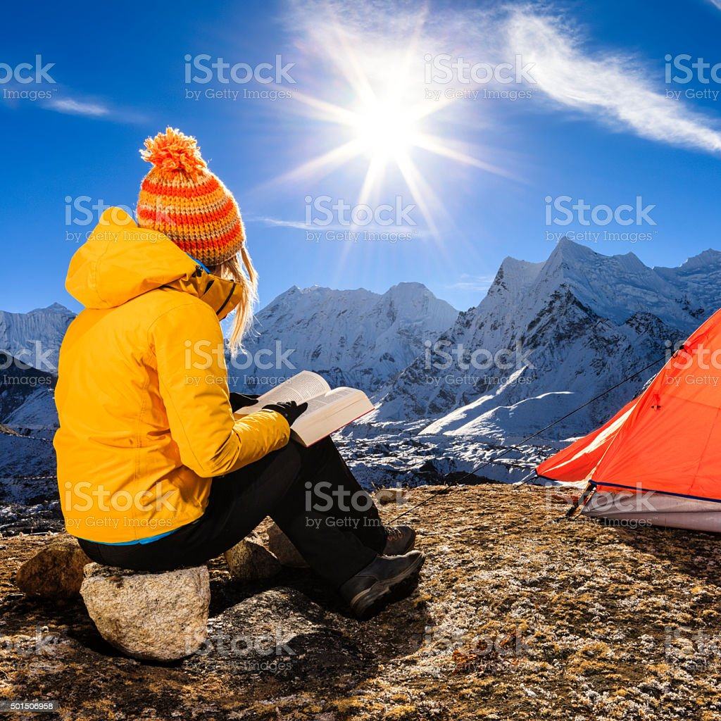Woman reading a book during sunrise over Himalayas, Everest Region stock photo