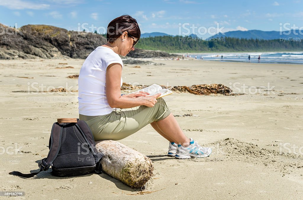Woman Reading a Book in Front of the Ocean stock photo