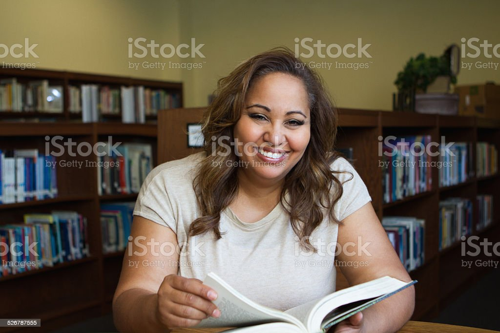Woman reading a book in the library stock photo