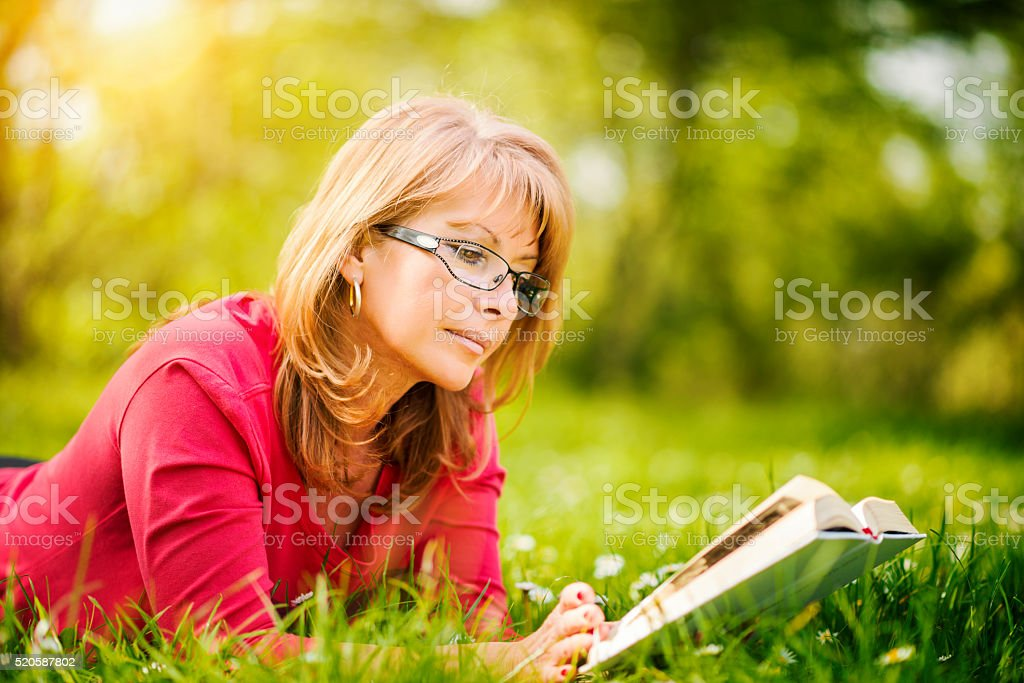 Woman reading a book in the park stock photo