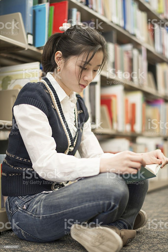Woman reading a book near bookshelf royalty-free stock photo