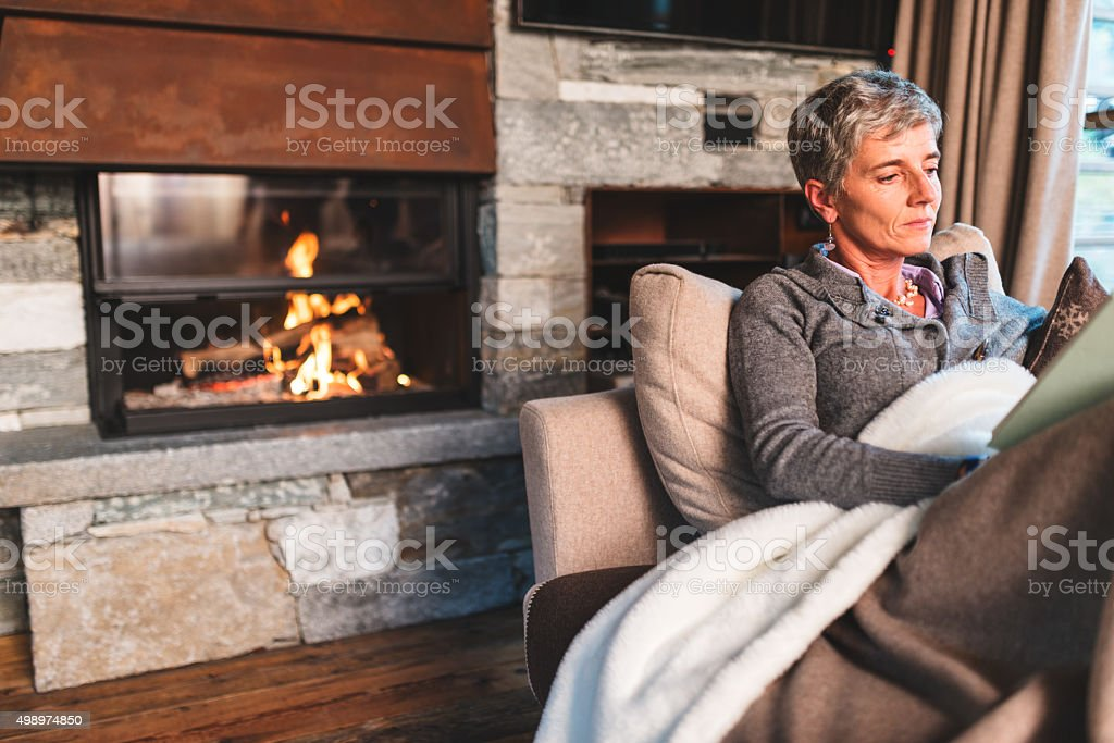 woman reading a book on the couch stock photo