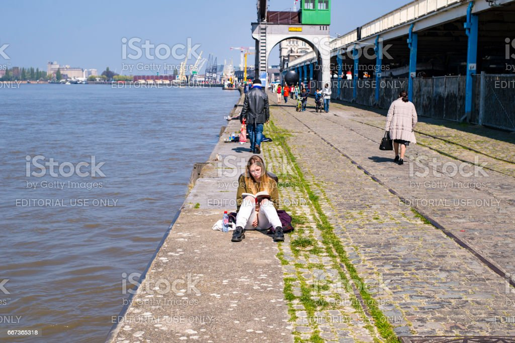 Woman reading a book on the docks of Antwerp stock photo