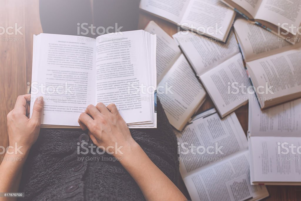 Woman reading a few books on the floor stock photo