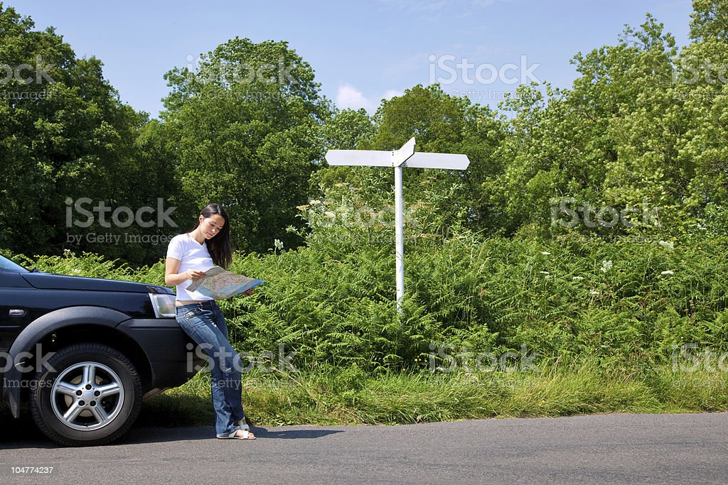 Woman reading a map by the roadside with blank signpost. stock photo