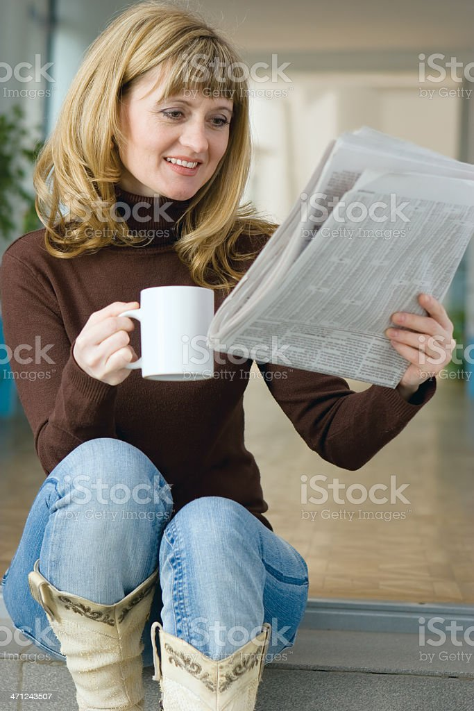 Woman reading a newspaper royalty-free stock photo