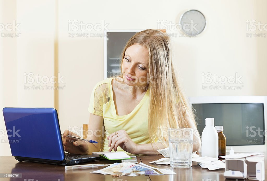 woman reading about medications on laptop in internet stock photo