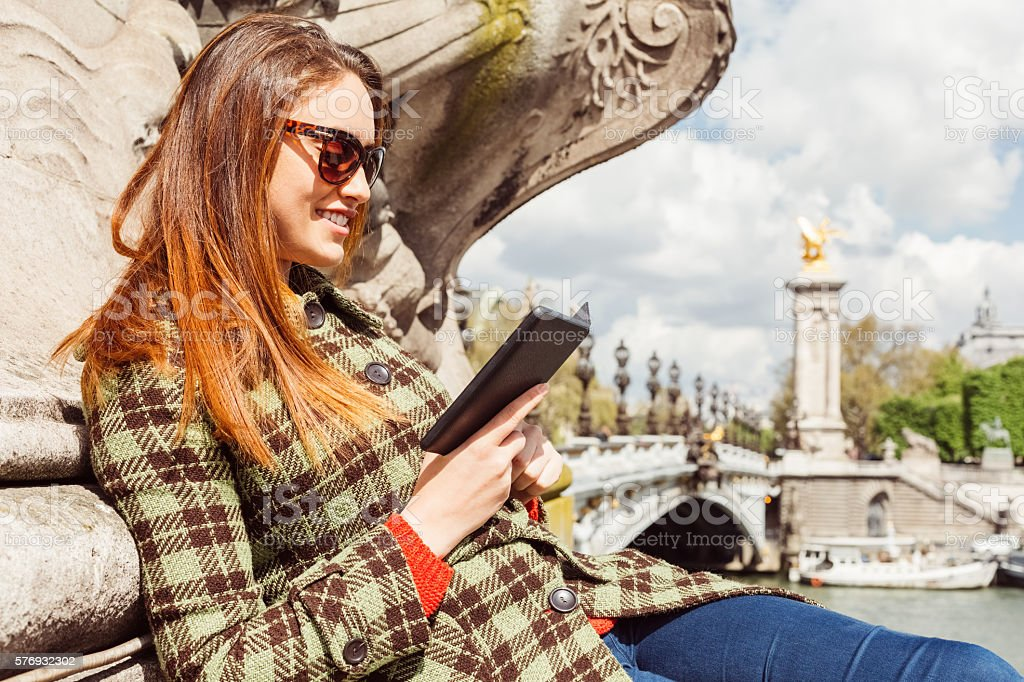 Woman reading an e-book near Seine river stock photo