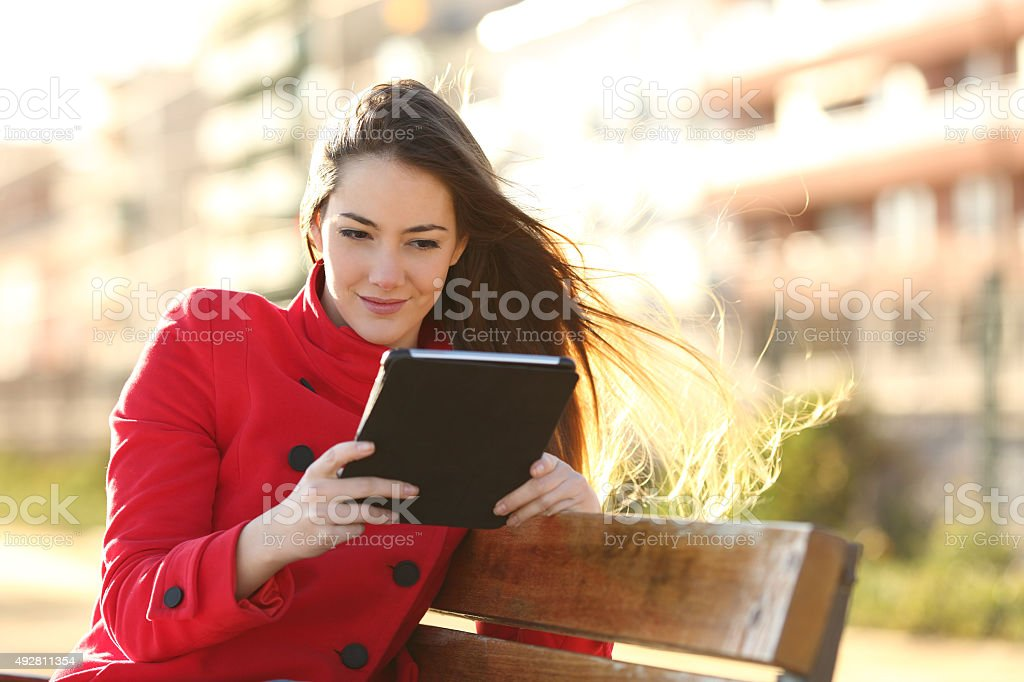 Woman reading an ebook or tablet in an urban park stock photo