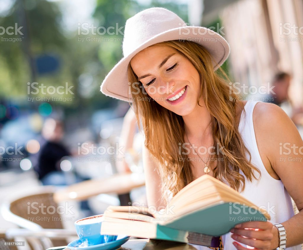 Woman reading at a cafeteria stock photo