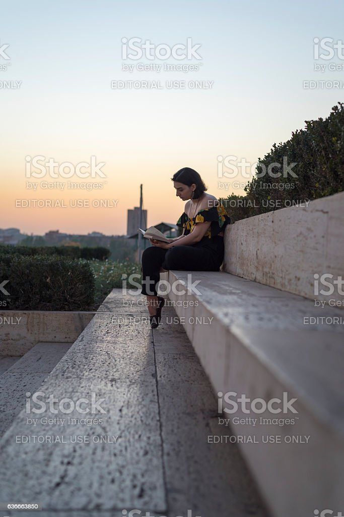 Woman reading book at Cascade steps in Yerevan, Armenia stock photo