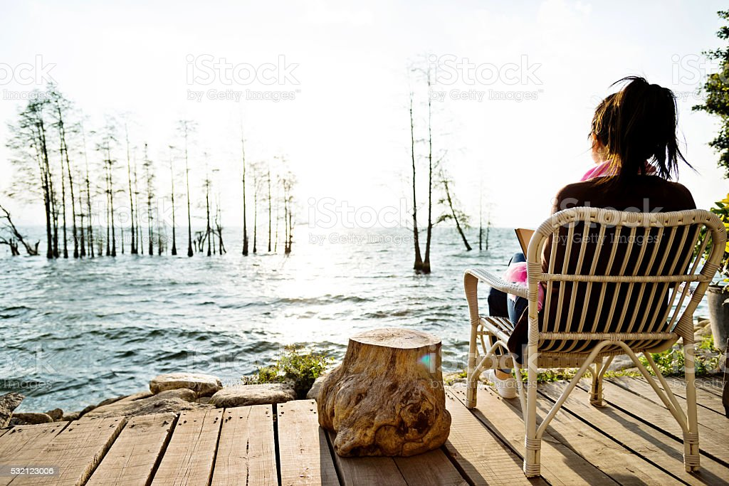 Woman reading book by the lake stock photo