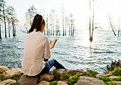 Woman reading book by the lake