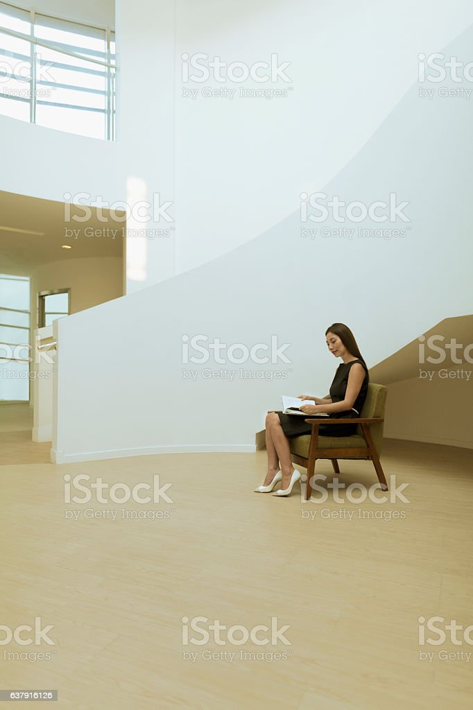 Woman reading book in modern building lobby stock photo