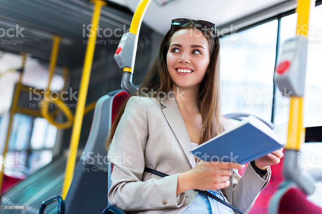 Woman reading book on bus stock photo
