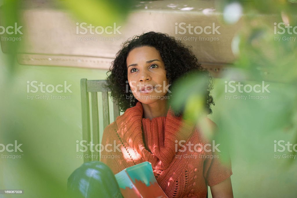 Woman reading book on patio royalty-free stock photo
