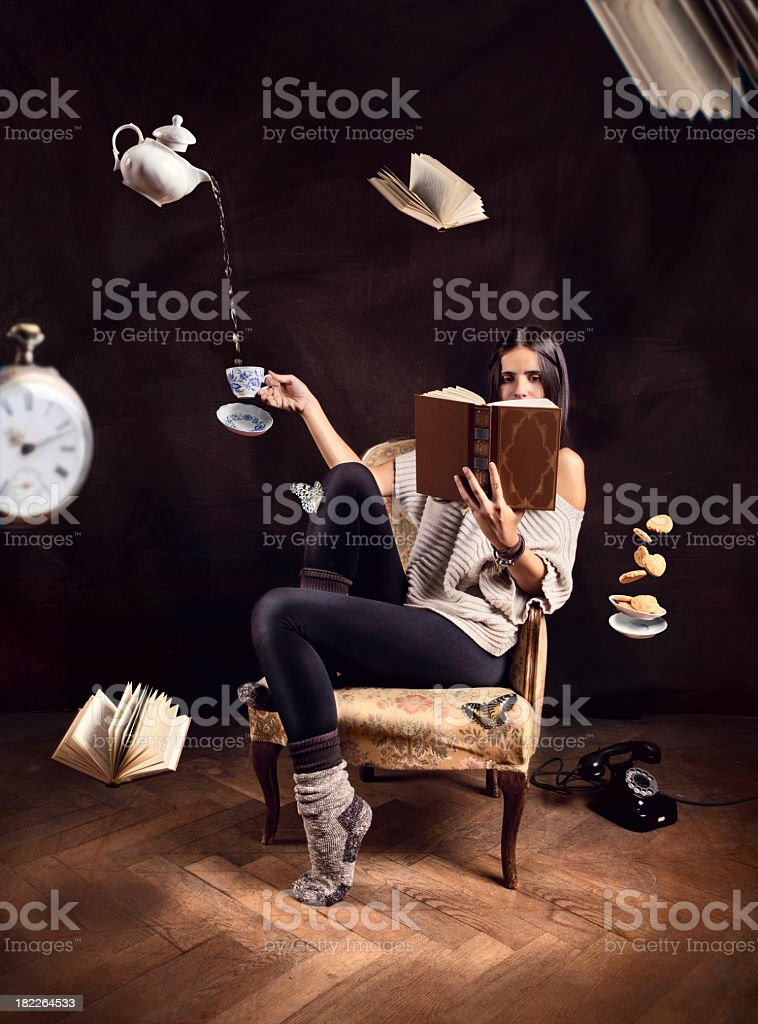 Woman reading book with abstract flying items around her stock photo