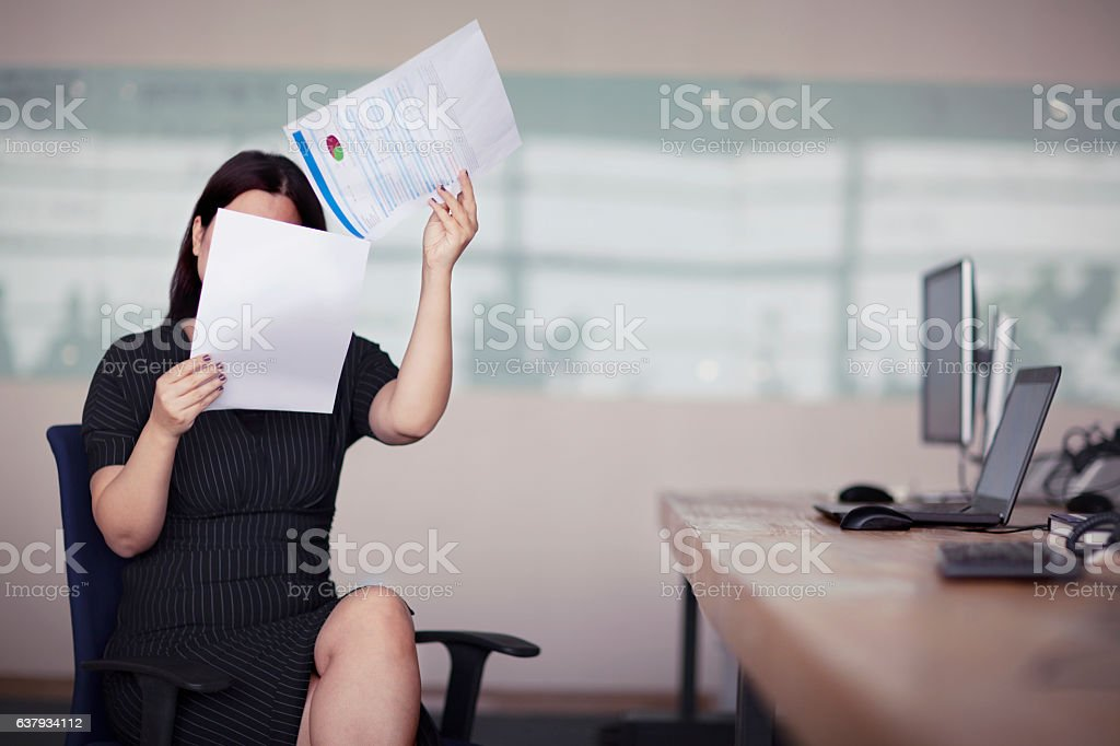 Woman reading business document covering face in office stock photo