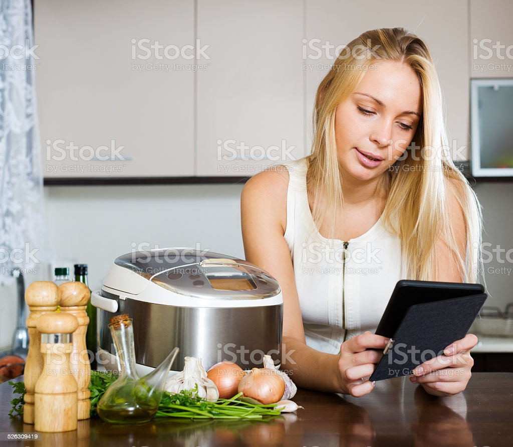 woman  reading ereader and cooking with  crockpot stock photo