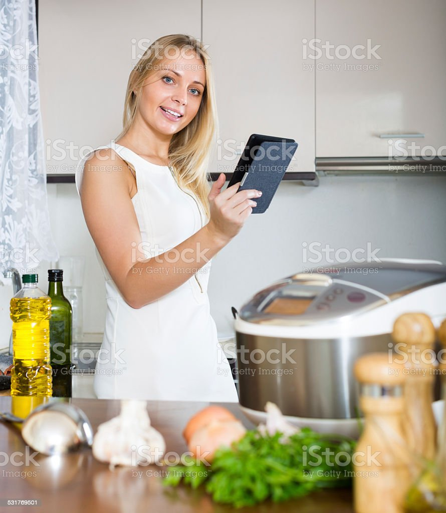 woman  reading ereader and cooking with new crockpot stock photo