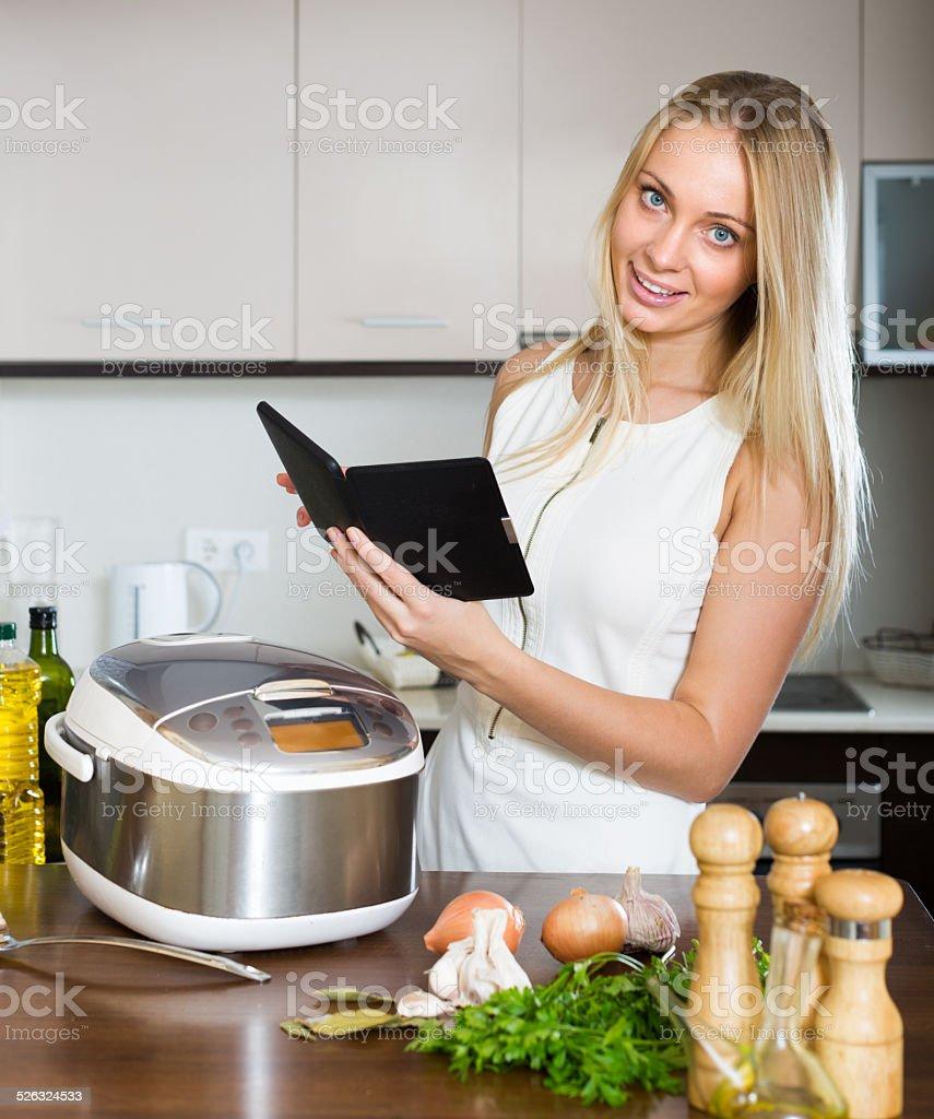 Woman reading ereader near multicooker stock photo