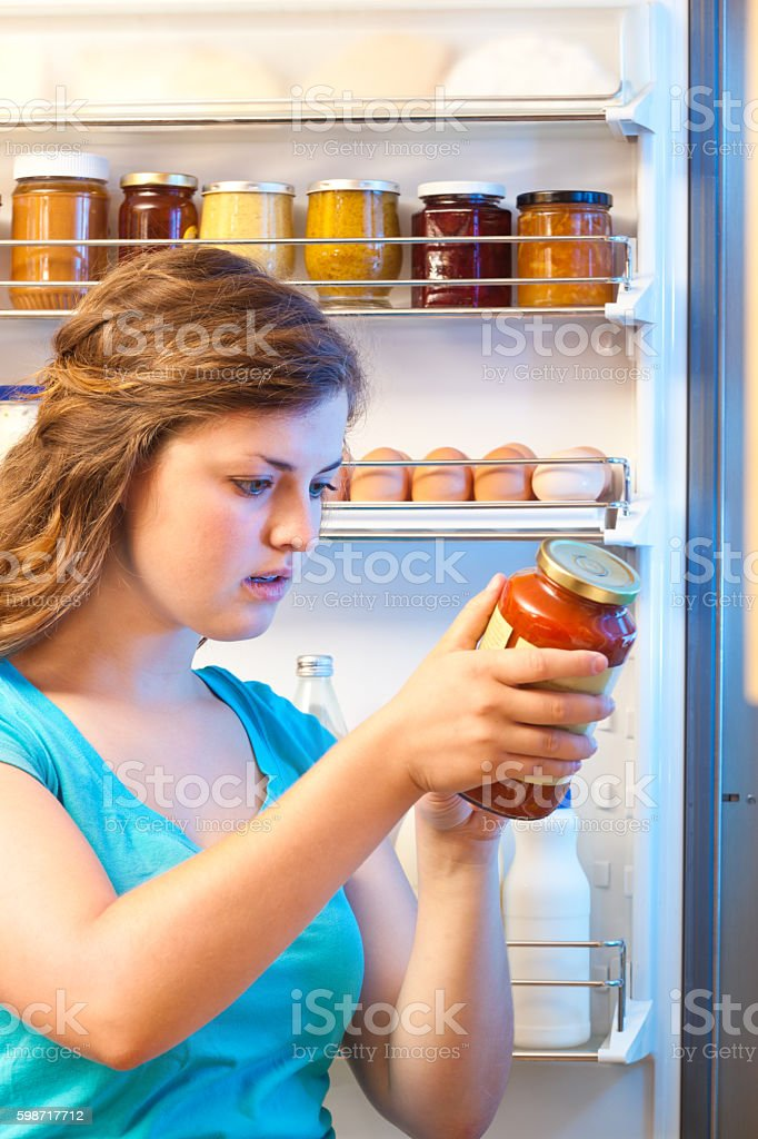 Woman Reading Food Label, Studying Ingredients by Open Refrigerator Door stock photo