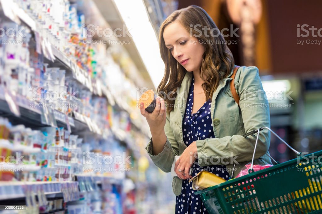 Woman reading food labels at grocery store stock photo