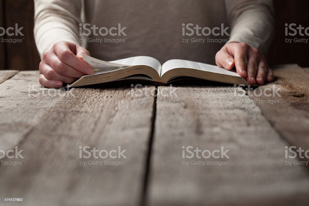 A woman reading her bible at a table  stock photo