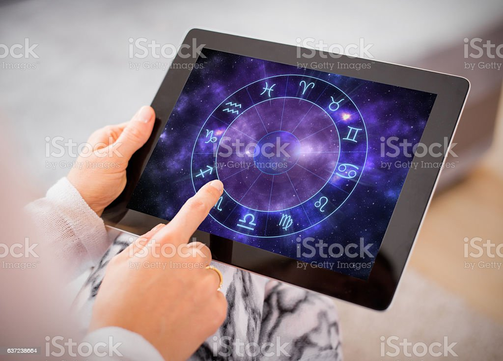 Woman reading horoscopes on tablet stock photo