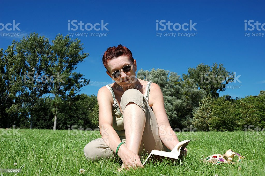 Woman reading in a park royalty-free stock photo