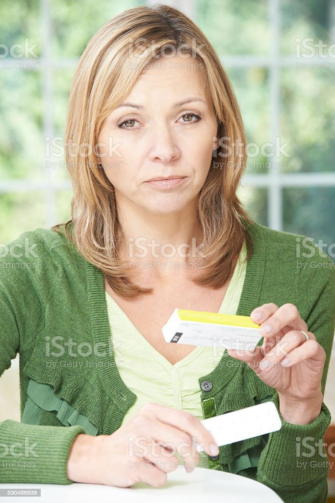 Woman Reading Information On Drug Packaging stock photo