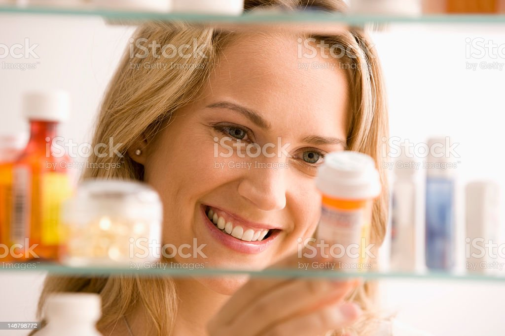 Woman reading instruction of a bottle of medicine royalty-free stock photo