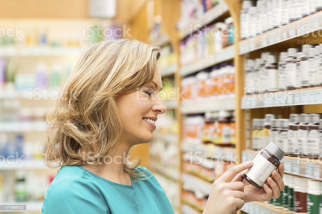 Woman Reading Instructions On Pill Bottle stock photo