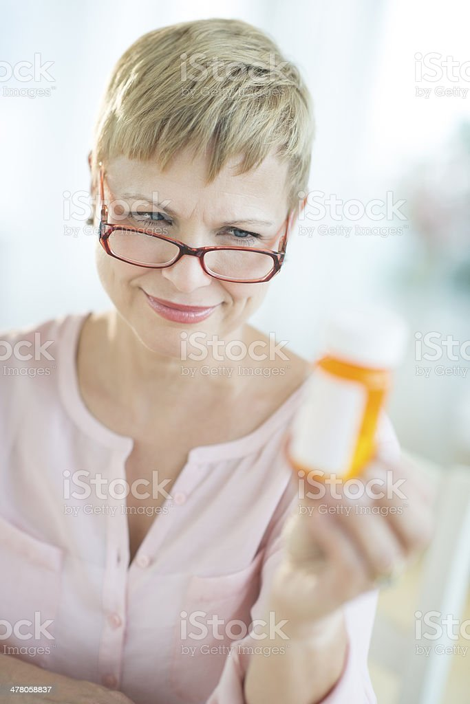 Woman Reading Instructions On Pill Bottle royalty-free stock photo
