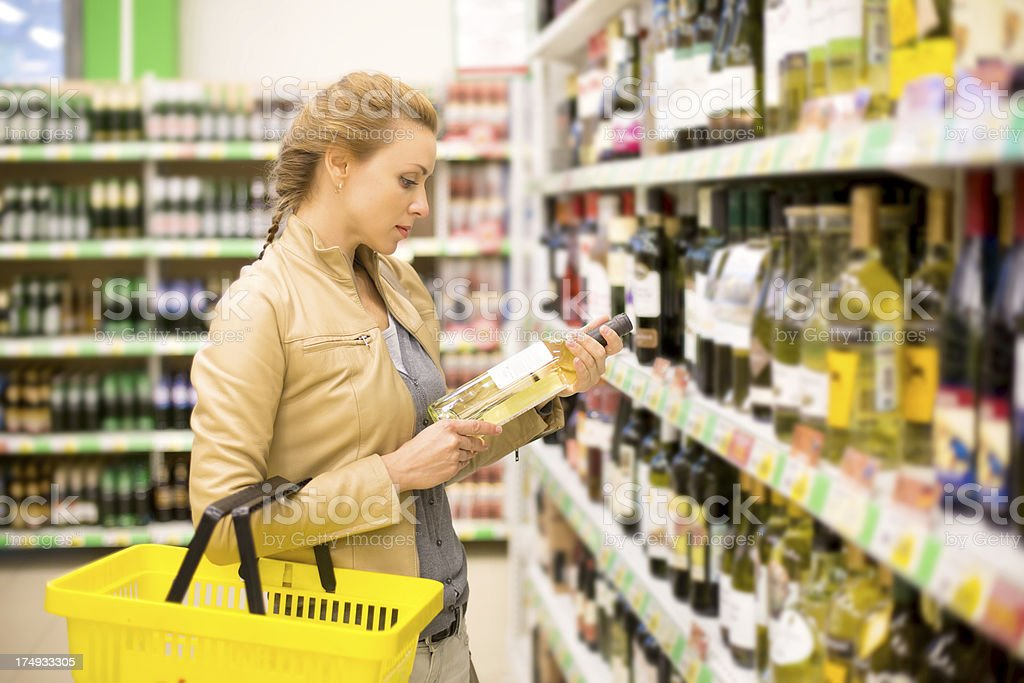 Woman reading label on a bottle of wine in a supermarket royalty-free stock photo