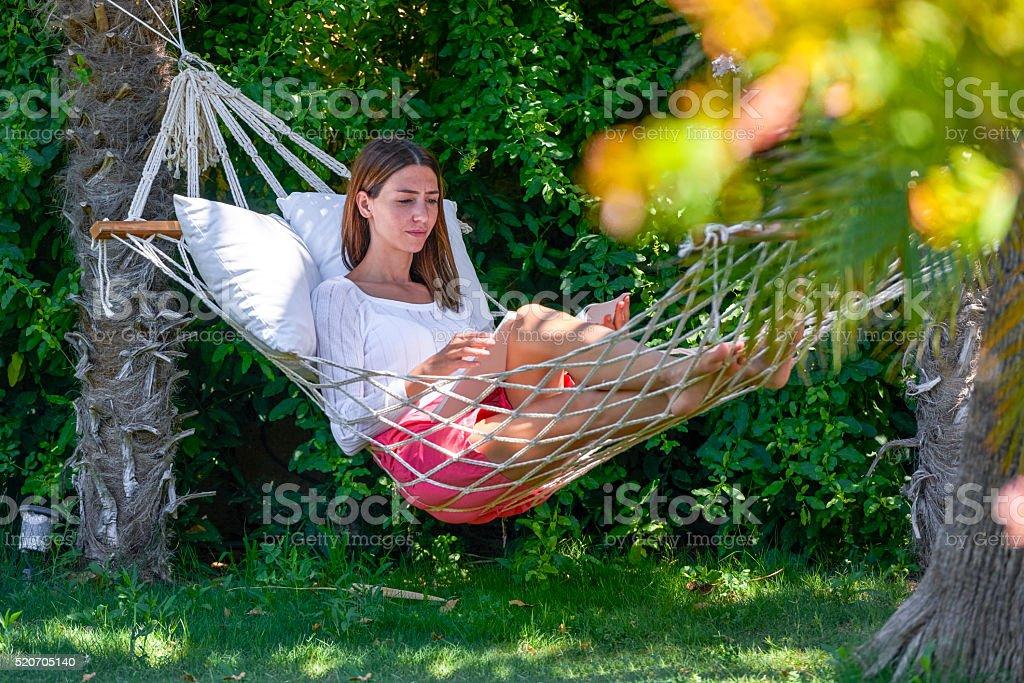 Woman reading magazine in hammock stock photo