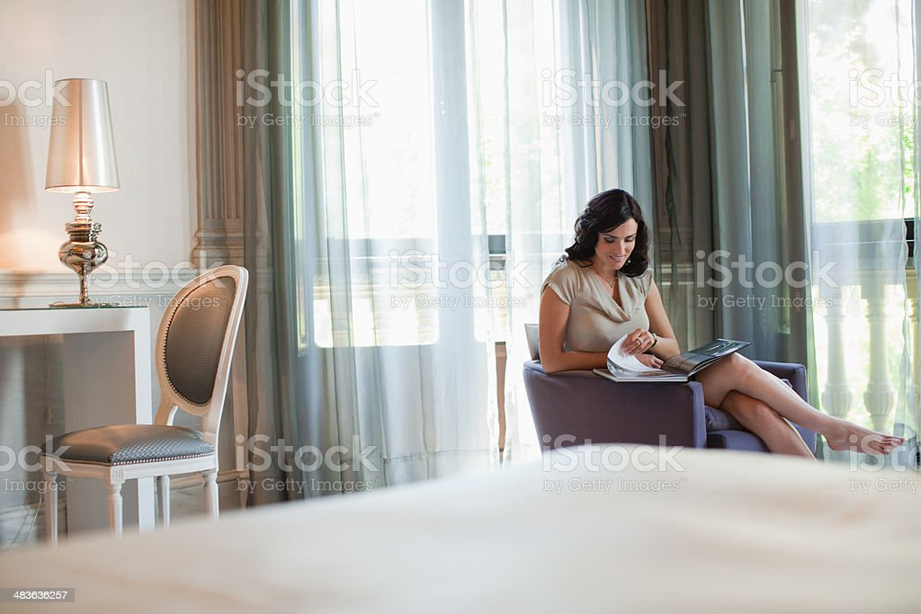 Woman reading magazine in hotel room stock photo