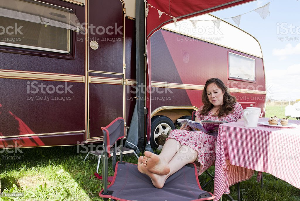 Woman reading magazine outside trailer stock photo