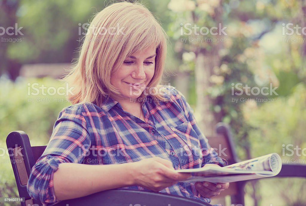 woman reading magazine stock photo