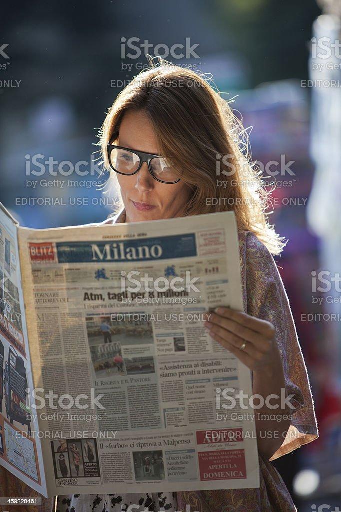 Woman reading Milano newspaper stock photo