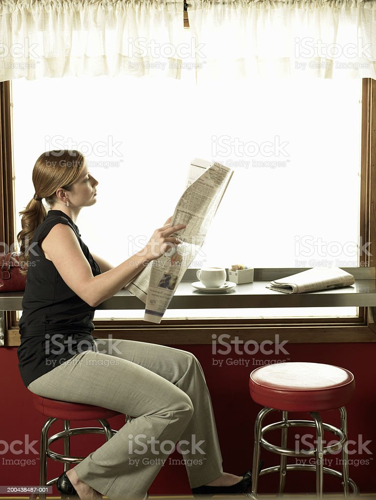 Woman reading newspaper in coffee shop royalty-free stock photo