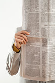 Woman reading newspaper on white background