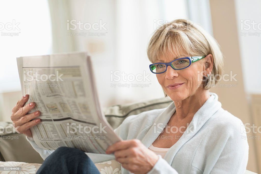 Woman Reading Newspaper While Relaxing On Sofa stock photo