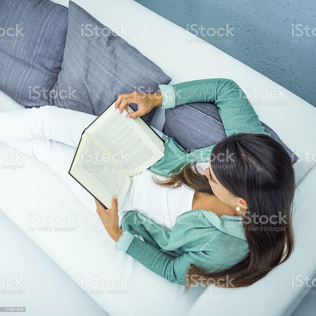 Woman reading on a white sofa royalty-free stock photo