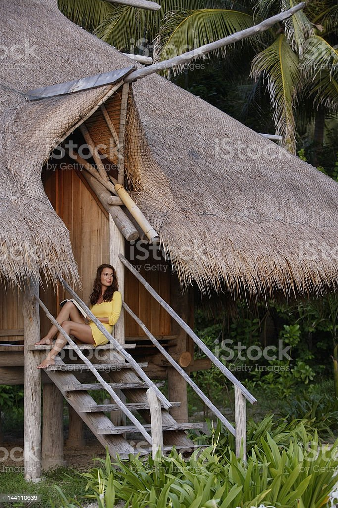 woman reading on steps of tropical home royalty-free stock photo