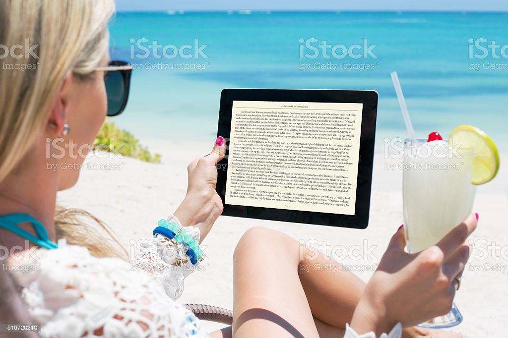 Woman reading  on tablet computer stock photo