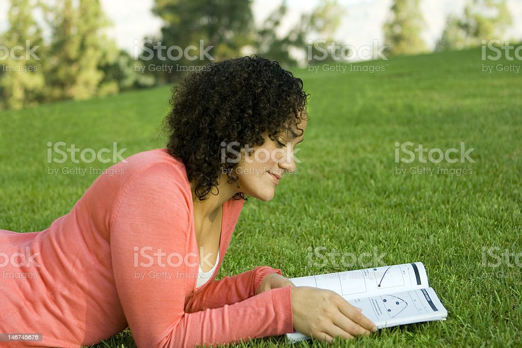 Woman Reading on the Grass stock photo