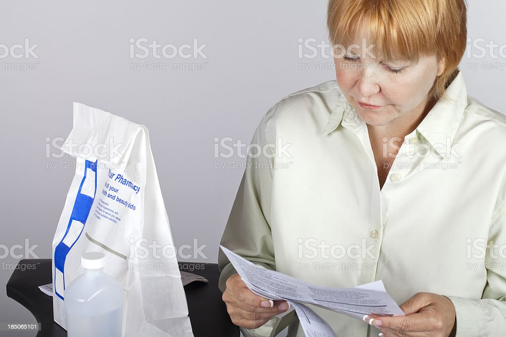 woman reading prescription directions stock photo